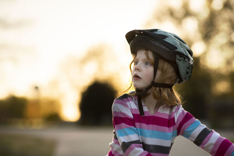 A five-year-old girl with red hair and blue eyes looks afar while riding her bike during an early spring evening while the sun sets behind her. One Person Focus On Foreground Child Leisure Activity Casual Clothing Childhood Looking Away Portrait Waist Up Looking Headshot Girls Helmet Sunset Cap Nature Headwear Standing Real People Outdoors Contemplation Innocence Bicycle Bike Bicycle Helmet Activity Fun Glowing 85mm F1.4 Lens Bokeh Bokeh Photography Stripes