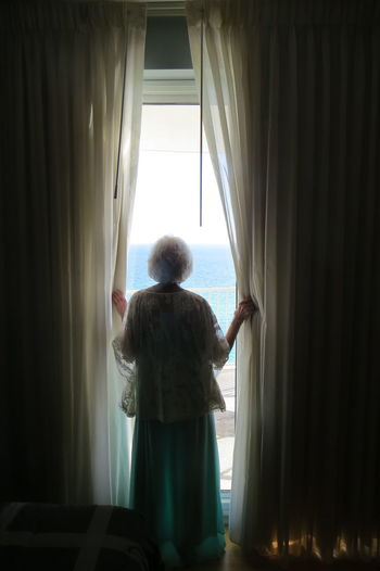 Emotional Photography Curtain Rear View Window Standing Indoors  One Person Adult Looking Through Window Women Solitude Looking Contemplation Moms & Dads Analogue Sound