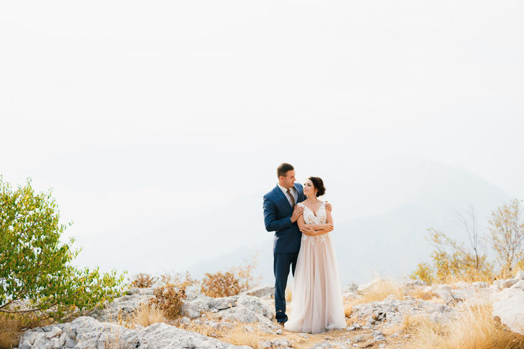 Front view of couple standing on rock