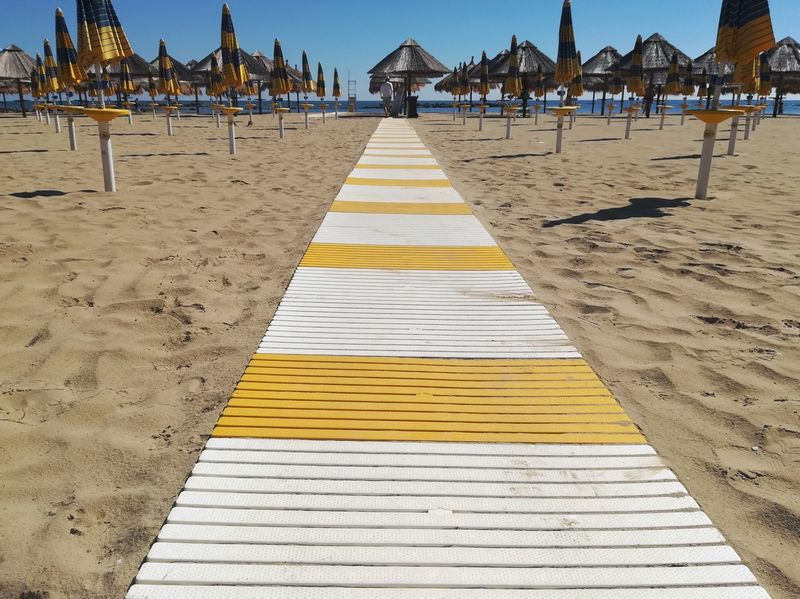 Seascape View Horizon Bathhouse Summer Holidays Pedestrian Crossing Pedestrian Walkway Beach Umbrellas Yellow And White Plastic Material Walkway On The Sand Gangway Perspective Personal Perspective Beach Sea Sand Clear Sky Sky Travel Beach Umbrella