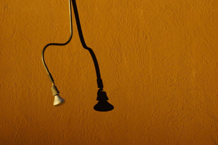 High angle view of light bulb hanging against yellow wall