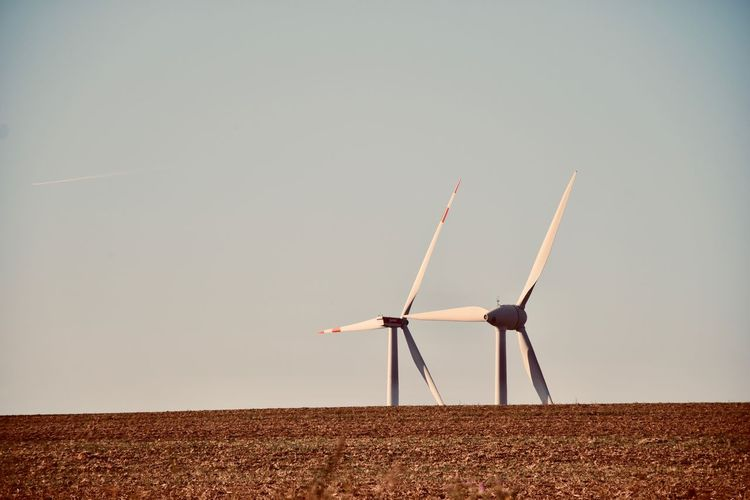 Windmills on field against clear sky