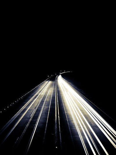 Light trails on highway against clear sky at night