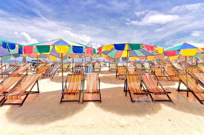 Deck Chairs And Parasols At Beach Against Cloudy Sky
