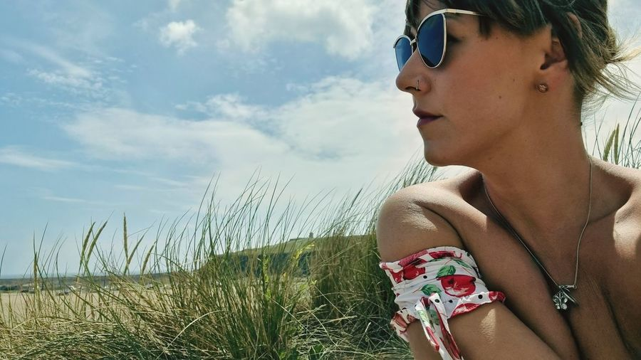 Young woman looking at sunglasses on beach