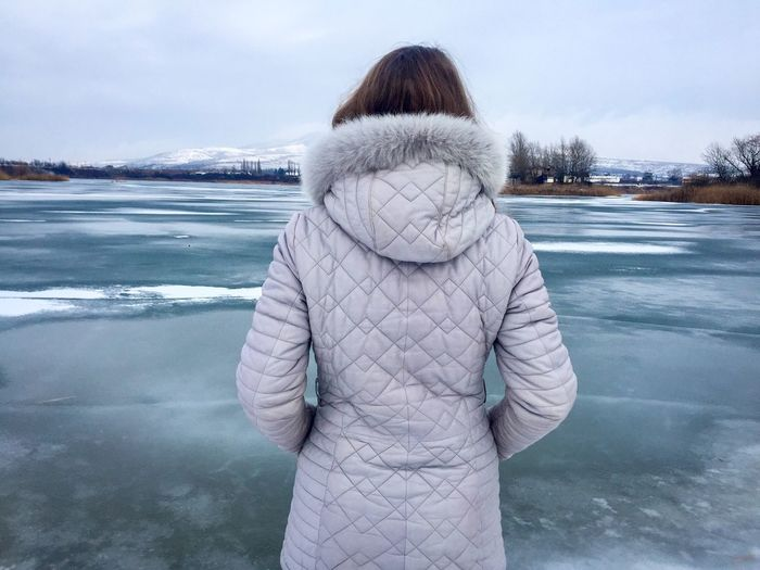 Back of woman wearing winter jacket near a frozen lake Winter Standing One Person Leisure Activity Warm Clothing Day Snow Sky Nature Outdoors Water People Woman Alone Lake Frozen Jacket Cold Ice Water Winter Snow Back
