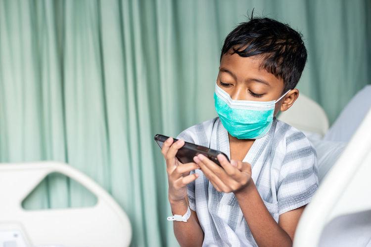 Full length of boy using mobile phone