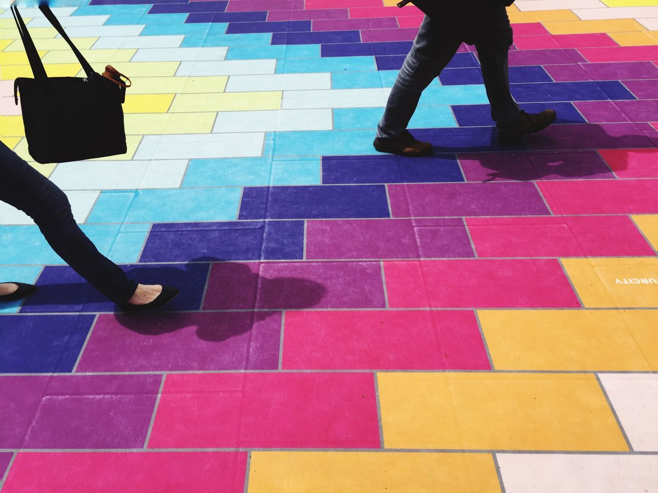 Low section of people walking on multi colored pattern floor