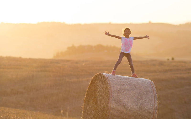 Full length of girl standing on hay bale