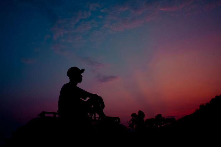Low angle view of silhouette man sitting against sky during sunset