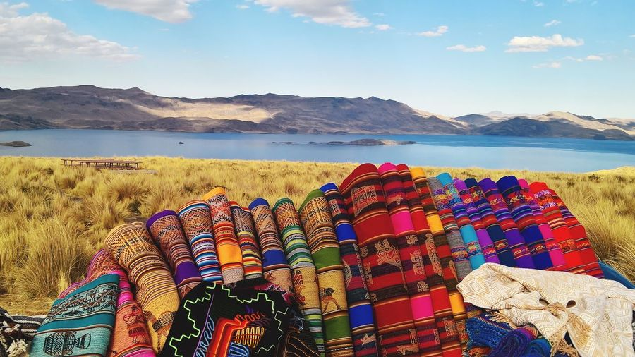 Colorful fabrics on grassy lakeshore with mountains in background against sky