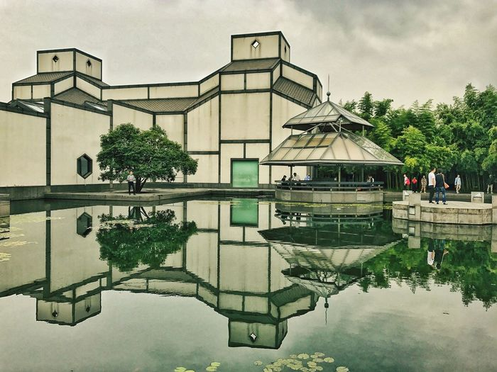 Suzhou Museum. Reflection Tree Water Reflecting Pool Sky Built Structure Outdoors Day Architecture Puddle Building Exterior Men Real People Nature People