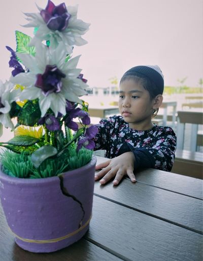 Woman looking at potted plant on table