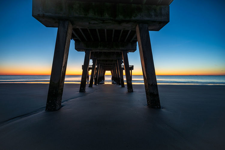 Pier on sea against sky during sunset