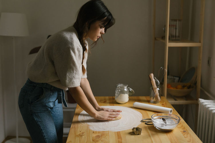 Side view of woman standing on table at home