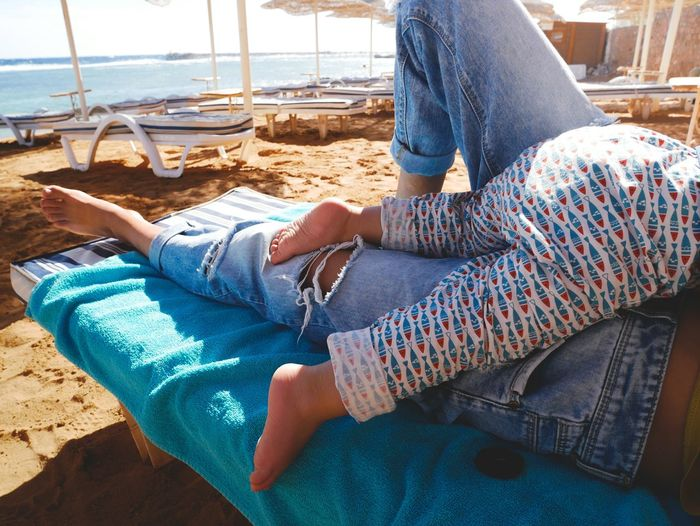 Low Section Of Baby Lying On Parent On Chair At Beach