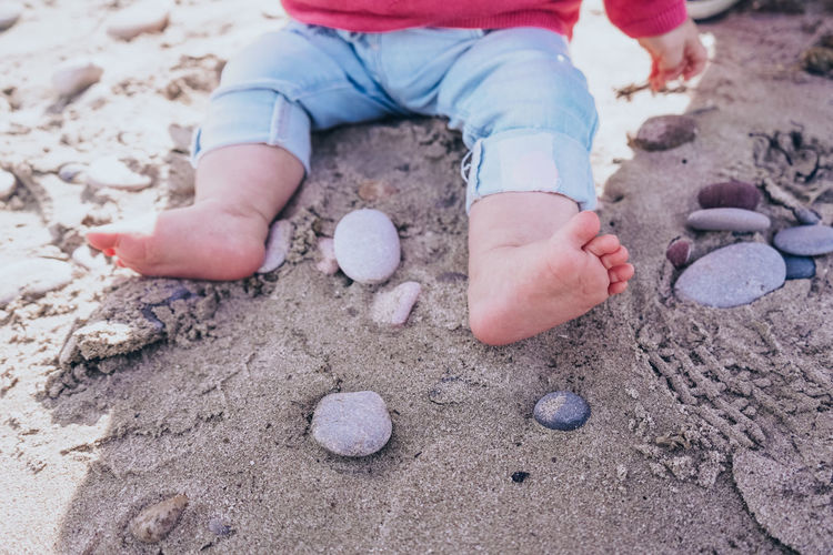 Low section of child playing on sand at beach