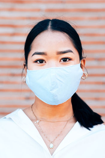 Close up portrait of young asian woman wearing face medical mask to prevent coronavirus infection