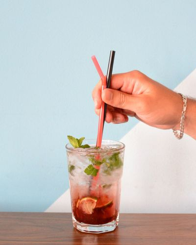 Close-Up Of Man Hand Holding Drinking Straws In Cold Drink Against Wall