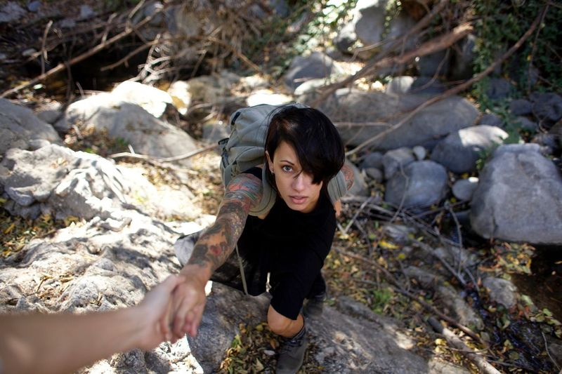 High angle portrait of female rock climber reaching for helping hand