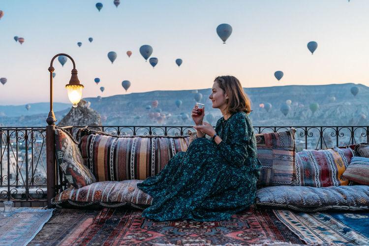 Full length of woman sitting on sofa against sky