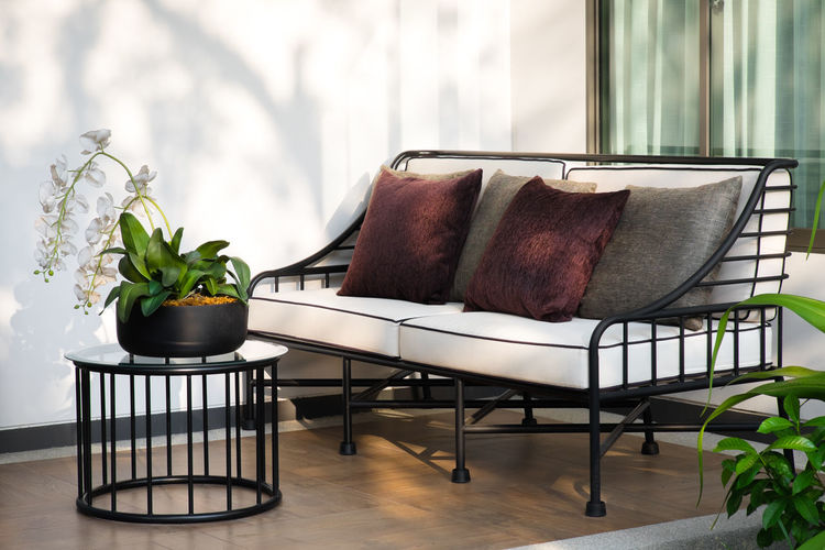 A modern white sofa in the home garden. Seat Chair Plant Furniture Indoors  Table Home Interior Potted Plant Pillow Vase Nature Absence Domestic Room Cushion Flower Flowering Plant Flooring Houseplant Armchair Coffee Table Sofa Garden Placeful Freshness