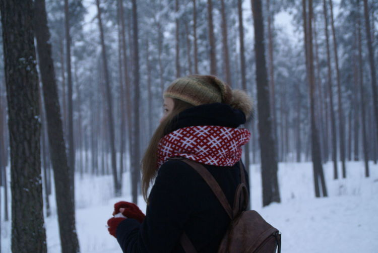 Side View Of Young Woman By Trees At Forest During Winter