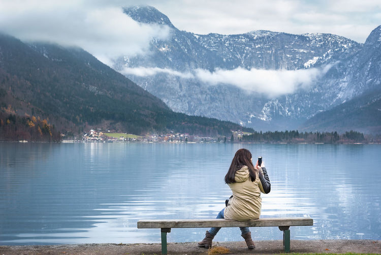 Woman sitting on a wooden bench, on the shores of the Hallstatter lake, using smartphone to photograph the Austrian Dachstein mountains, in Hallstatt, Austria. Austria Austrian Alps Cold Temperature Hallstatt Hallstatt, Austria Hallstattersee Idyllic Lake Mountain Mountain Range Nature Outdoors Photography Themes Relaxation Scenics Sitting Technology Tranquil Scene Water Women Wooden Bench Young Woman