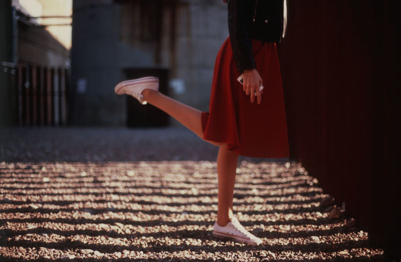 Low Section Of Woman Standing On One Leg Outdoors