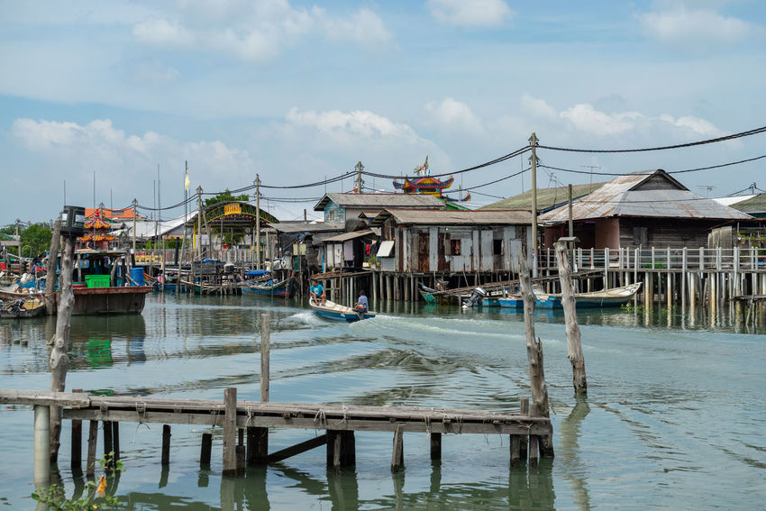 A view of a fishermen's village on stilts besides the sea in Pulau Ketam (Crab Island). This island is famous for sea food products and restaurants. Architecture Building Building Exterior Built Structure Cloud - Sky Crab Island Day House Mode Of Transportation Nature Nautical Vessel No People Outdoors Pulau Ketam Malaysia Reflection Residential District Sky Stilt House Transportation Water Waterfront Wooden Post