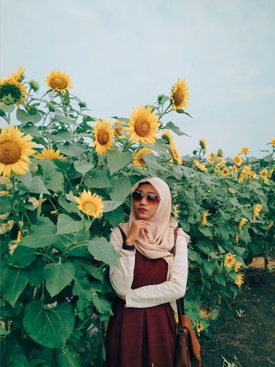 Portrait of young woman standing against sunflower