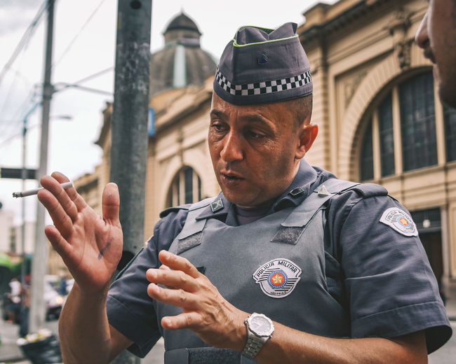 A police man giving us directions in Sao Paulo. Authority Bulletproof Cigarette  City Close-up Communication Communications Tower Directions Front View Gesturing Military Occupation One Person Police Police Force Policeman Portrait Real People Standing The Portraitist - 2017 EyeEm Awards Uniform Urban Vest Watch Work The Street Photographer - 2017 EyeEm Awards BYOPaper! Adventures In The City