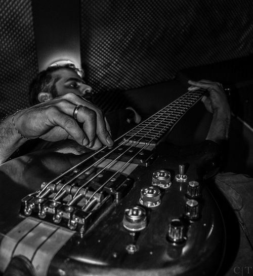 Low angle view of musician playing guitar during concert at night