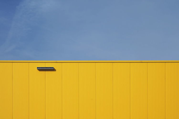 Low angle view of yellow wall against blue sky