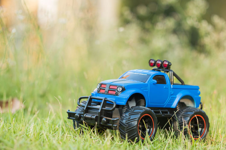 A scene of Blue RC Off-road truck car (Radio-controlled) is parked on the green grass with blurred meadow background. (This toy has some dust from children playing) 4x4 Automobile Fun Monster Monster Trucks Nature RC Transportation Travel Activity Adventure Car Childhood Day Grass Green Color Meadow Nature Off-road Vehicle Offroad Outdoors Race Remote Toy Toy Car