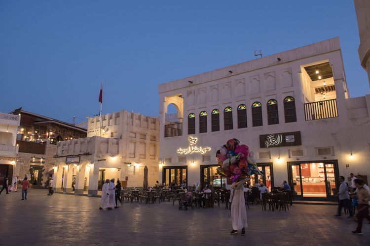Souq Waqif Architectural Column Architecture Building Building Exterior Built Structure City Clear Sky Crowd Dusk Group Of People Illuminated Large Group Of People Men Nature Night Outdoors Qatar Real People Sky Souk Tourism Travel Travel Destinations Waqif Women