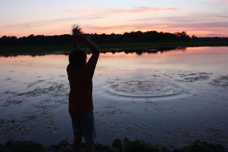 Rear view of man looking at lake during sunset