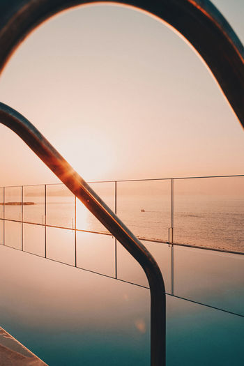 Railing by sea against clear sky during sunset
