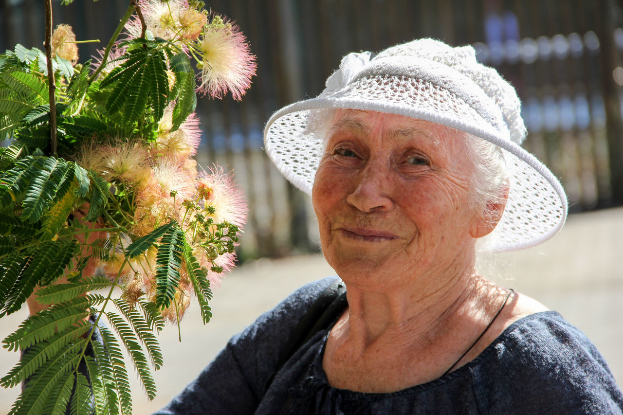 Close-Up Portrait Of Senior Woman Standing By Albizia Julibrissin Flowers During Sunny Day