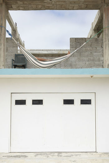 Low angle view of person relaxing on hammock at incomplete building