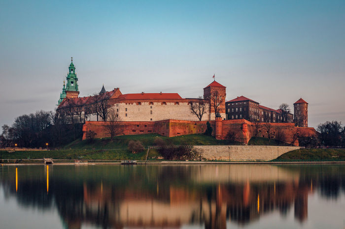 The Wawel castle at dusk in the old town of Krakow. Ancient Castle Poland Riverside Vistula Architecture Building Exterior Built Structure Day History Krakow Medieval Nature No People Outdoors Reflection River Sky Travel Destinations Tree Water Waterfront