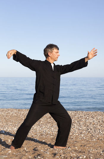 Man practicing Tai Chi – Posture Single Whip Exercising Man Martial Arts Qi Gong Shadow Boxing Tai Chi Tai Chi Chuan Taiji Arms Outstretched Arms Raised barefoot Beach Full Length Healthy Lifestyle Mature Men One Man Only One Mature Man Only One Person Outdoors Posture Practicing Sand Sport Taijiquan Wushu