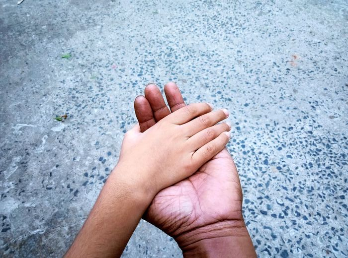 Close-up of hands of a person and a boy