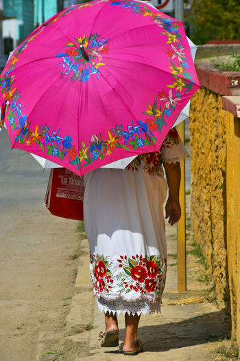 Indigenous woman walking with umbrella in Yucatan, Mexico Adult Clothing Day Floral Pattern People Protection Real People Rear View Traditional Clothing Umbrella Vivid, Pink, Ba Walking, Shopping, Yucatan, Mexico, Indigenous Women