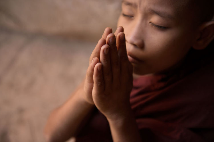 High angle view of boy with hands clasped praying