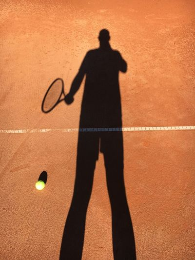 Shadow Of Man Holding Tennis Racket And Standing At Court