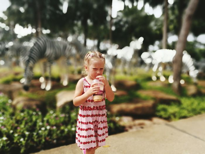 Portrait of little girl drinking juice at park