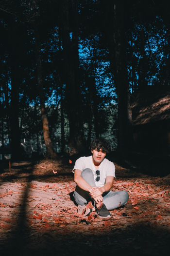 Young man sitting on land in forest