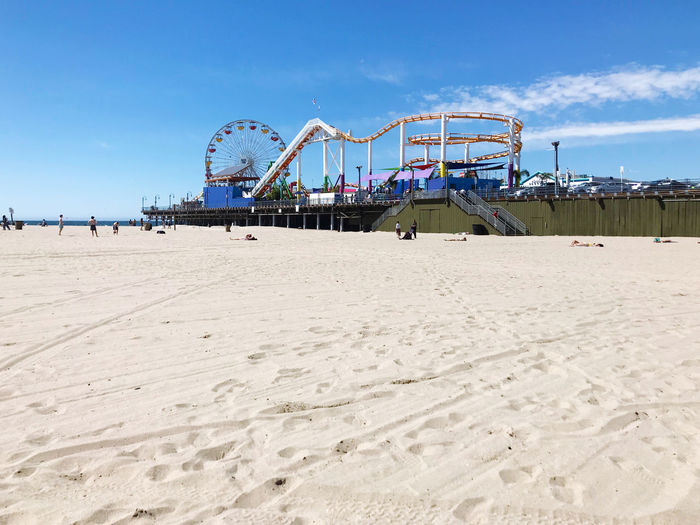 Ferris wheel on beach against blue sky