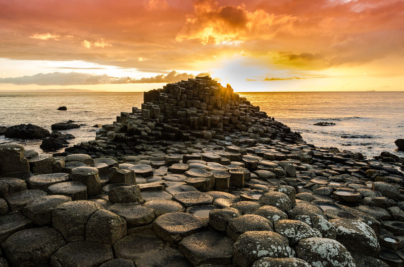 Stacked rocks at beach against sky during sunset